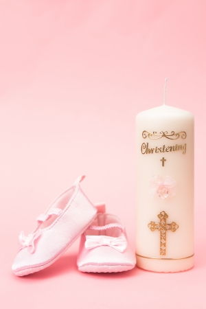 Christening candle with pink baby booties on pink background photo