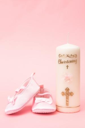 Taufkerze mit rosa Baby Booties auf rosa Hintergrund