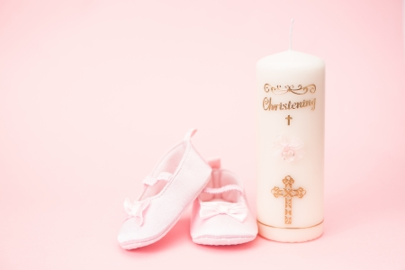 Christening candle with pink baby booties and copy space on pink background photo
