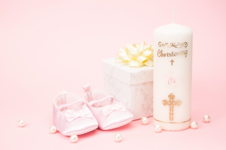 Christening candle with pink baby booties and gift box on pink background with pearls photo