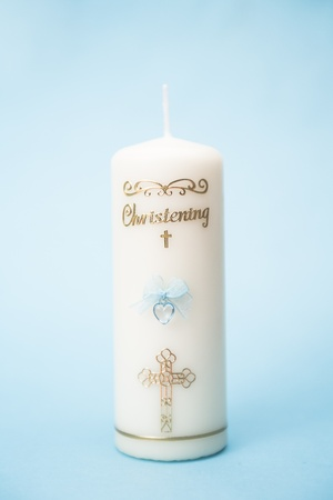 Christening candle for a boy with blue detail on blue background photo