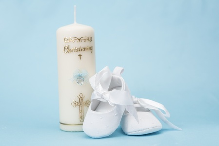 baptism background: Christening candle for a boy with white baby booties on blue background Stock Photo
