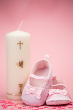 Pink baby booties with christening candle on pink background  photo