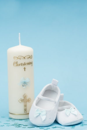 Baby booties with blue ribbon and christening candle on blue background with copy space photo