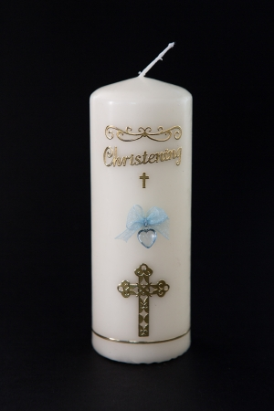 White christening candle with blue detail on black background photo