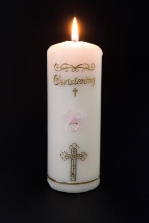 Leuchtet weiß Taufkerze mit rosa Detail auf schwarzem Hintergrund Standard-Bild