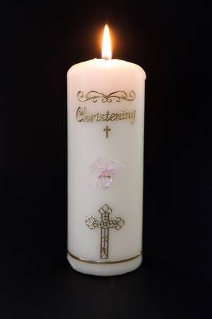 Lit white christening candle with pink detail on black background photo