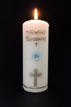 Lit white christening candle with blue detail on black background photo