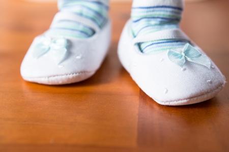 first step: Baby in blau und wei� booties unter ersten Schritt auf Holzboden Lizenzfreie Bilder