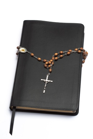 jehovah: Rosary beads wrapped around the bible on white background