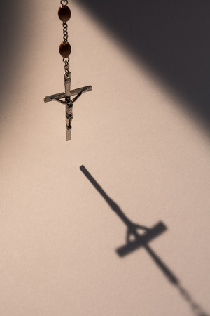 Crucifix from rosary beads hanging and casting a shadow photo