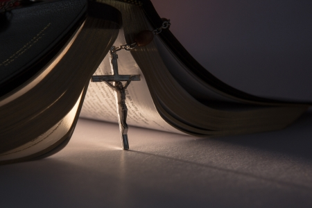 Crucifix from rosary beads propping open the bible  photo