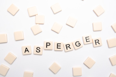Asperger spelled out in plastic letter pieces on white background Stock Photo - 18129620