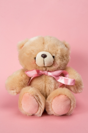 Teddy bear with pink ribbon on pink background photo