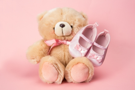 Fluffy teddy with pink ribbon and baby booties on pink background photo