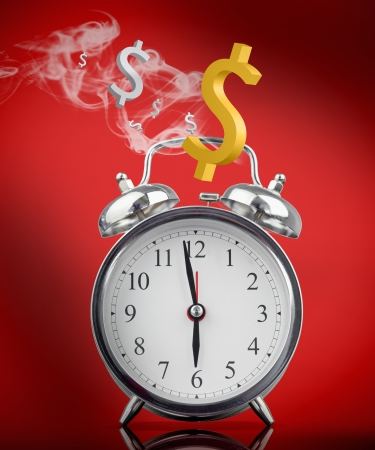 Smoking hot alarm clock with dollar signs on red background photo