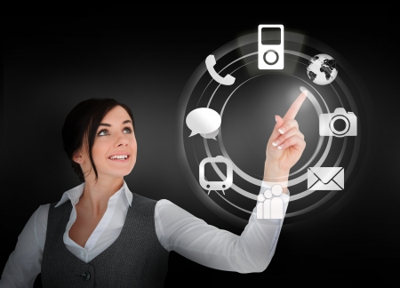 Businesswoman using wheel interface for applications on black background photo