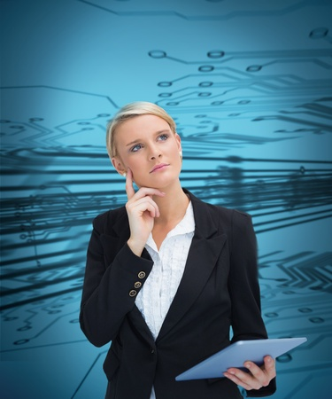 Thoughtful businesswoman holding tablet on blue circuit background photo