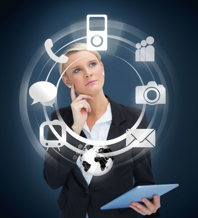 computer generated: Thoughtful businesswoman with tablet pc considering various applications on navy background