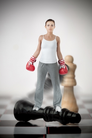 knocked over: Female boxer standing on black chess piece on chessboard