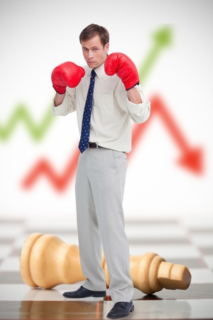 Businessman in boxing gloves on chessboard with red and green arrow in background photo