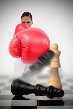 knocked out: Woman in boxing gloves knocking over chess pieces on chess board