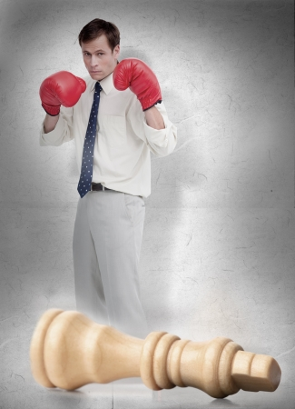 knocked over: Businessman in red boxing gloves with knocked over white chess piece
