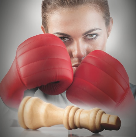 knocked over: Powerful female boxer with knocked white chess piece on chessboard
