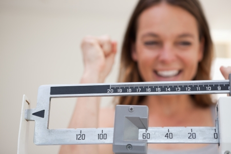 losses: Scale showing weight loss to smiling woman