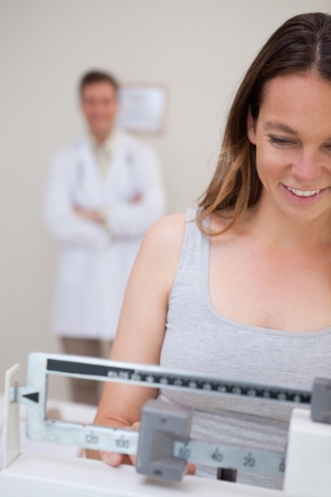 Weight measuring woman being supervised by doctor photo