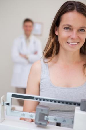 physical exam: Donna sorridente sulla scala di essere supervisionato da medico