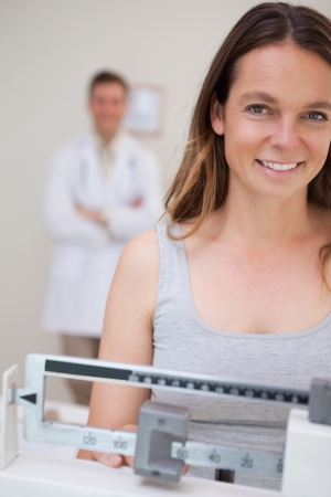 Smiling woman on the scale being supervised by doctor photo