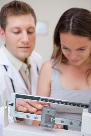 adjusted: Scale being adjusted by doctor and patient Stock Photo