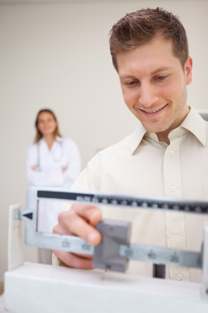 Man adjusting scale while being supervised by doctor photo