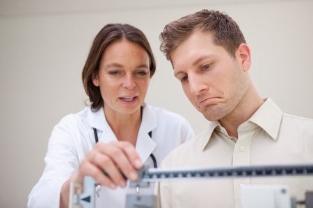 Doctor and patient measuring weight together photo