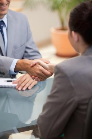 estrechando manos: Hombre de negocios y empresaria que sacuden las manos en una oficina
