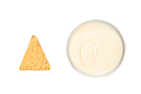 nacho: A bowl of white dip and a nacho placed side by side Stock Photo