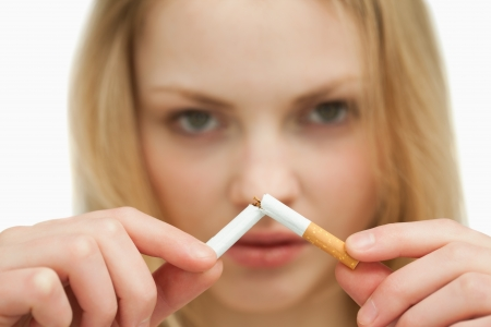 detrimental: Close up of a young woman breaking a cigarette against white background Stock Photo