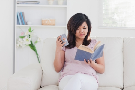 Woman holding a mug and a book in a living room photo