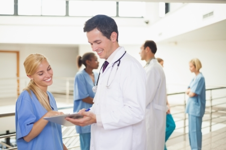 Smiling doctor showing a clipboard to nurse in hospital corridor photo