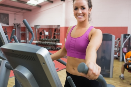 Smiling brunette stepping on a step machine in gym photo