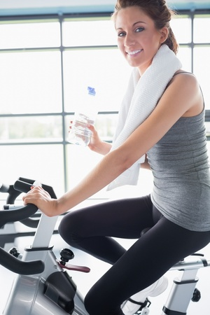 Woman riding an exercise bike and drinking a bottle of water photo