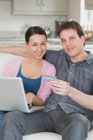 Couple sitting on the couch using the credit card while working on the laptop photo