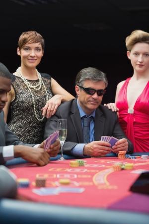 Man in sunglasses smiling at poker table in casino photo