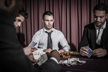 high stakes: Serious man looking up from high stakes poker game in casino