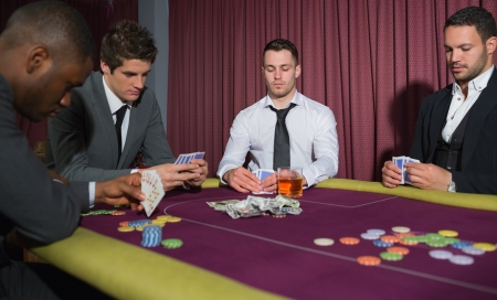 high stakes: Men playing high stakes game of poker in casino Stock Photo