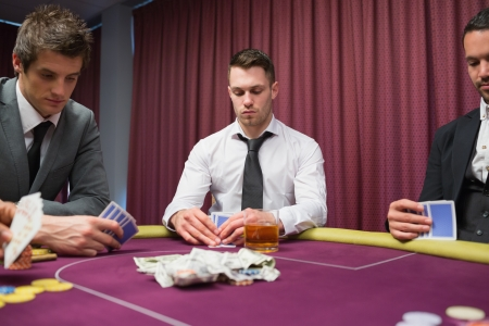 high stakes: Men looking at their hands in high stakes poker game in casino