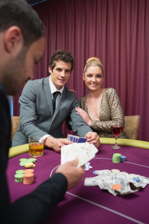 high stakes: Happy couple playing poker in casino