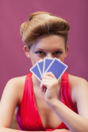 Woman sitting at table in a casino while holding cards before her face photo