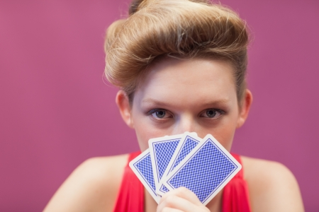 Woman sitting at table in a casino and holding cards up to her face Stock Photo - 18466651
